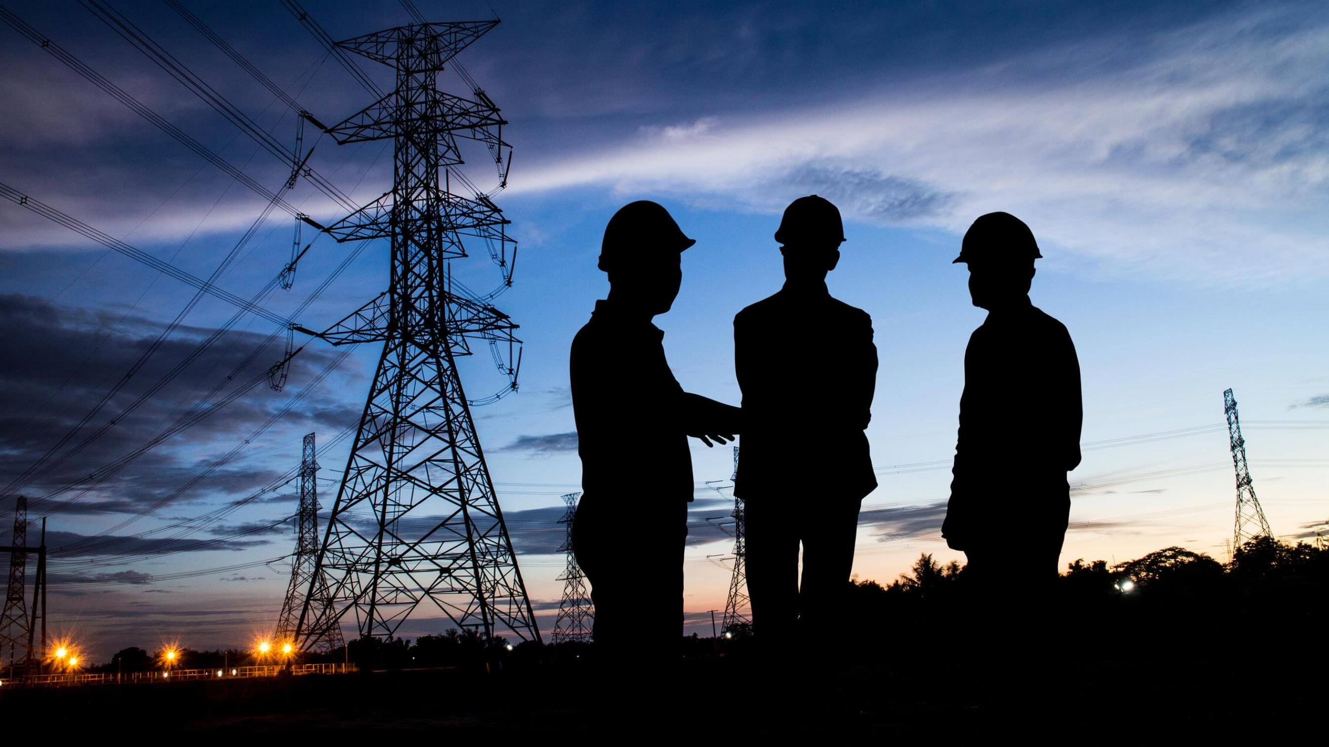Silouette of three men in evening in front of transmission tower