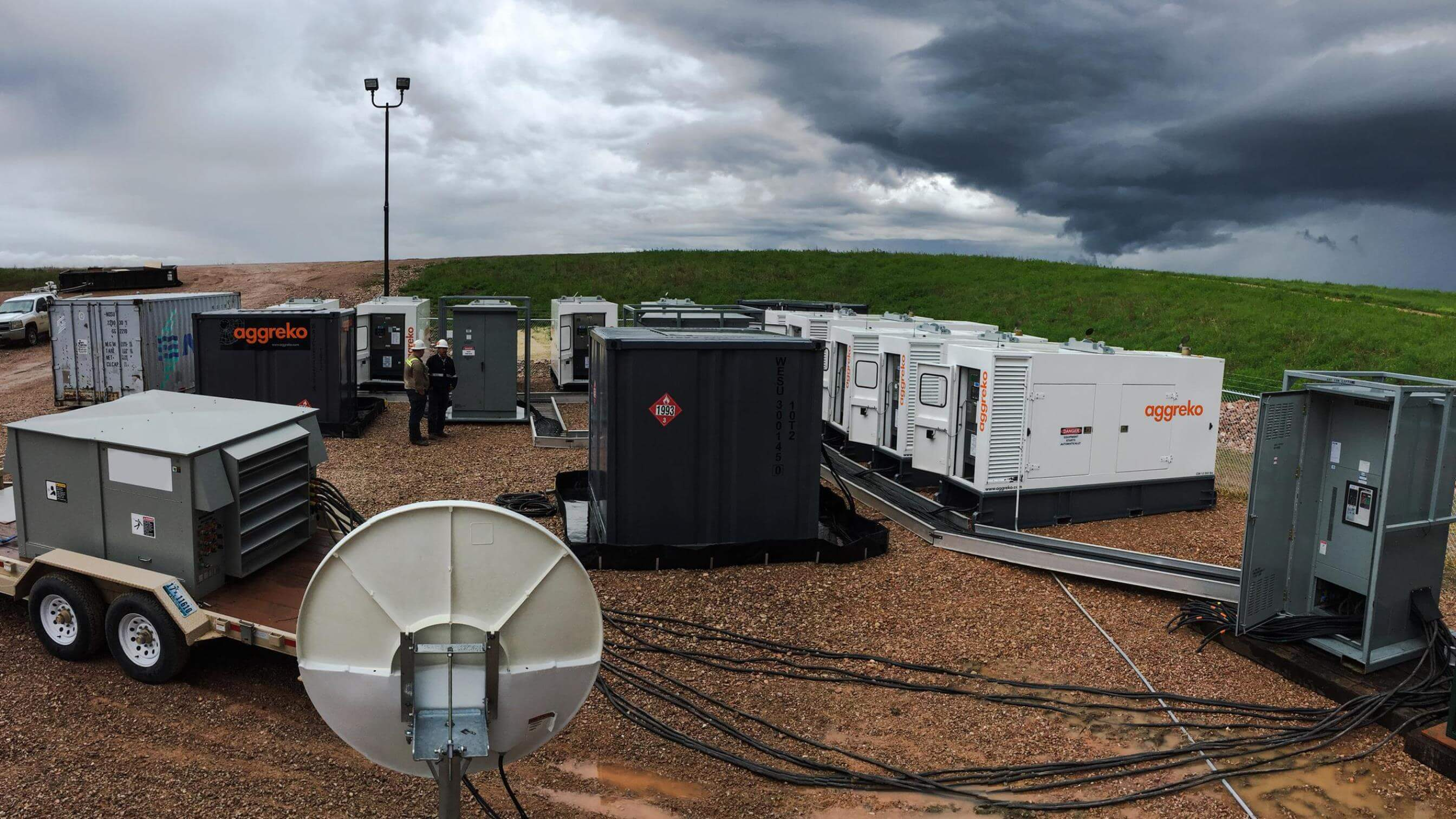 Aggreko equipment in a field under a stormy sky