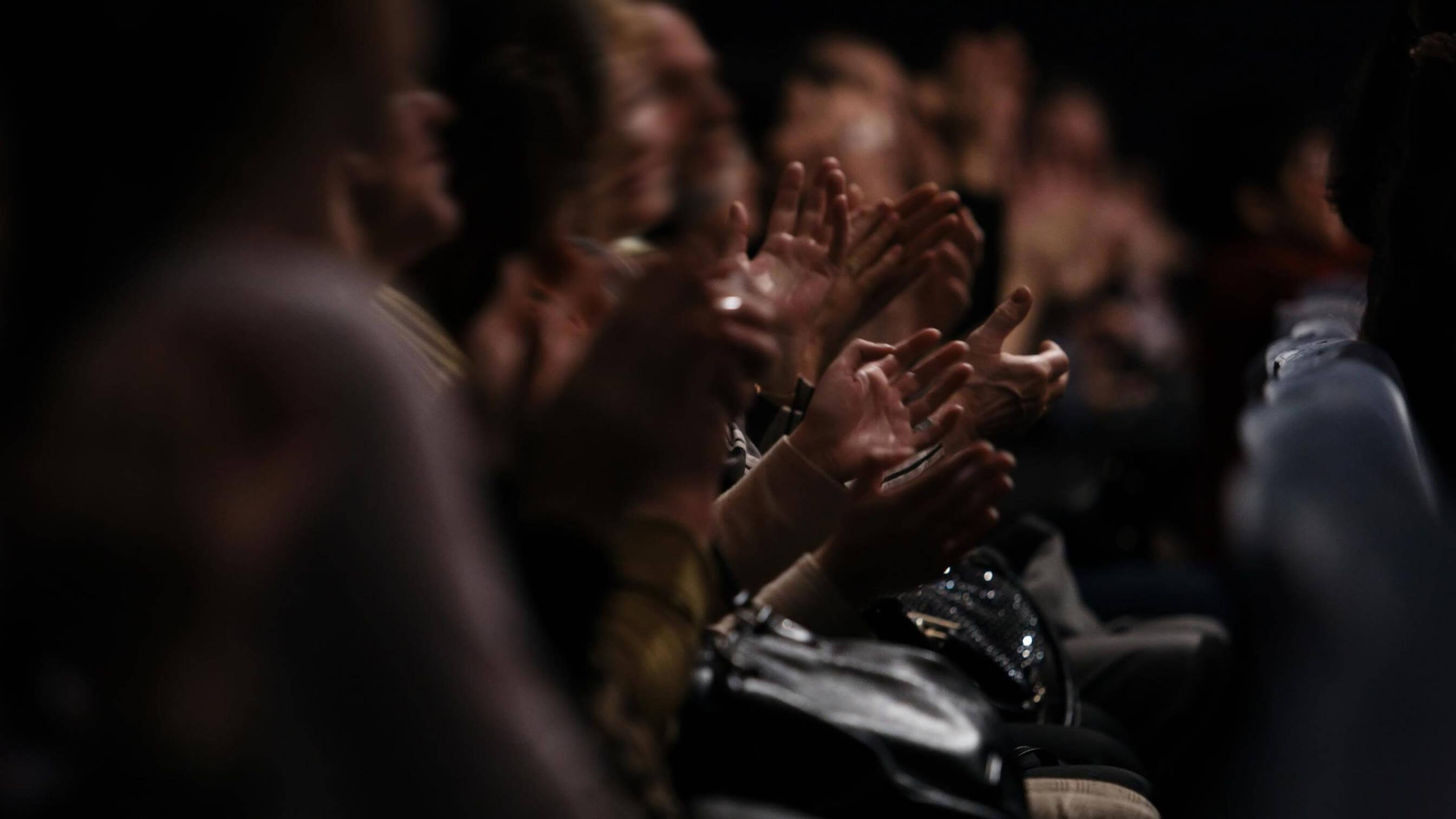 Audience clapping in darkened theatre
