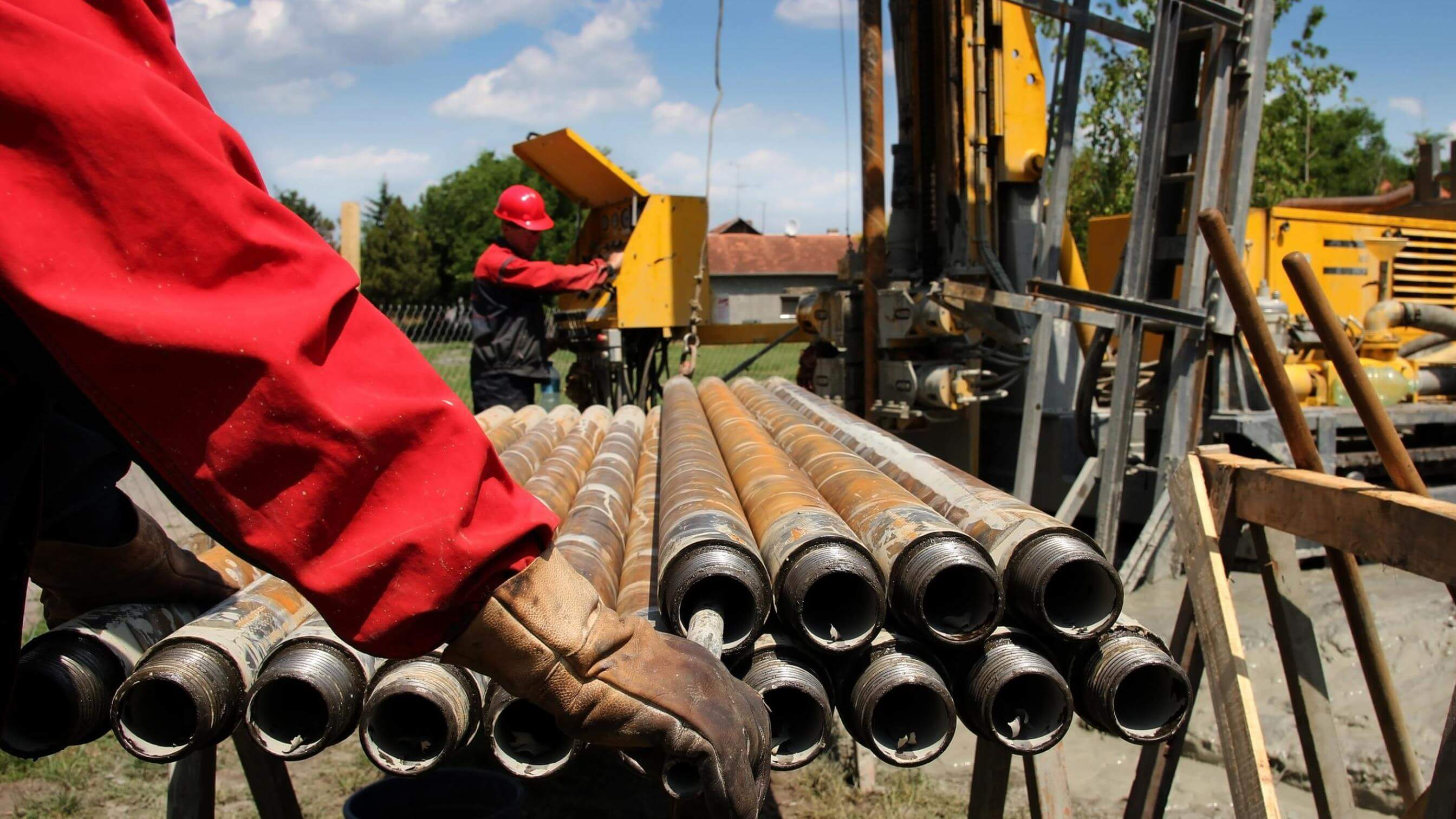 Drilling workers moving oil pipes
