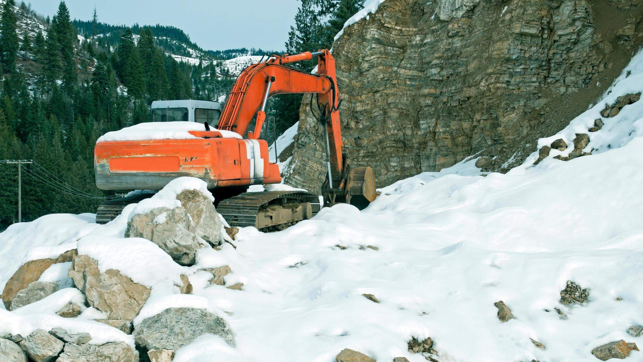 Excavator digging on a snowy mountainside