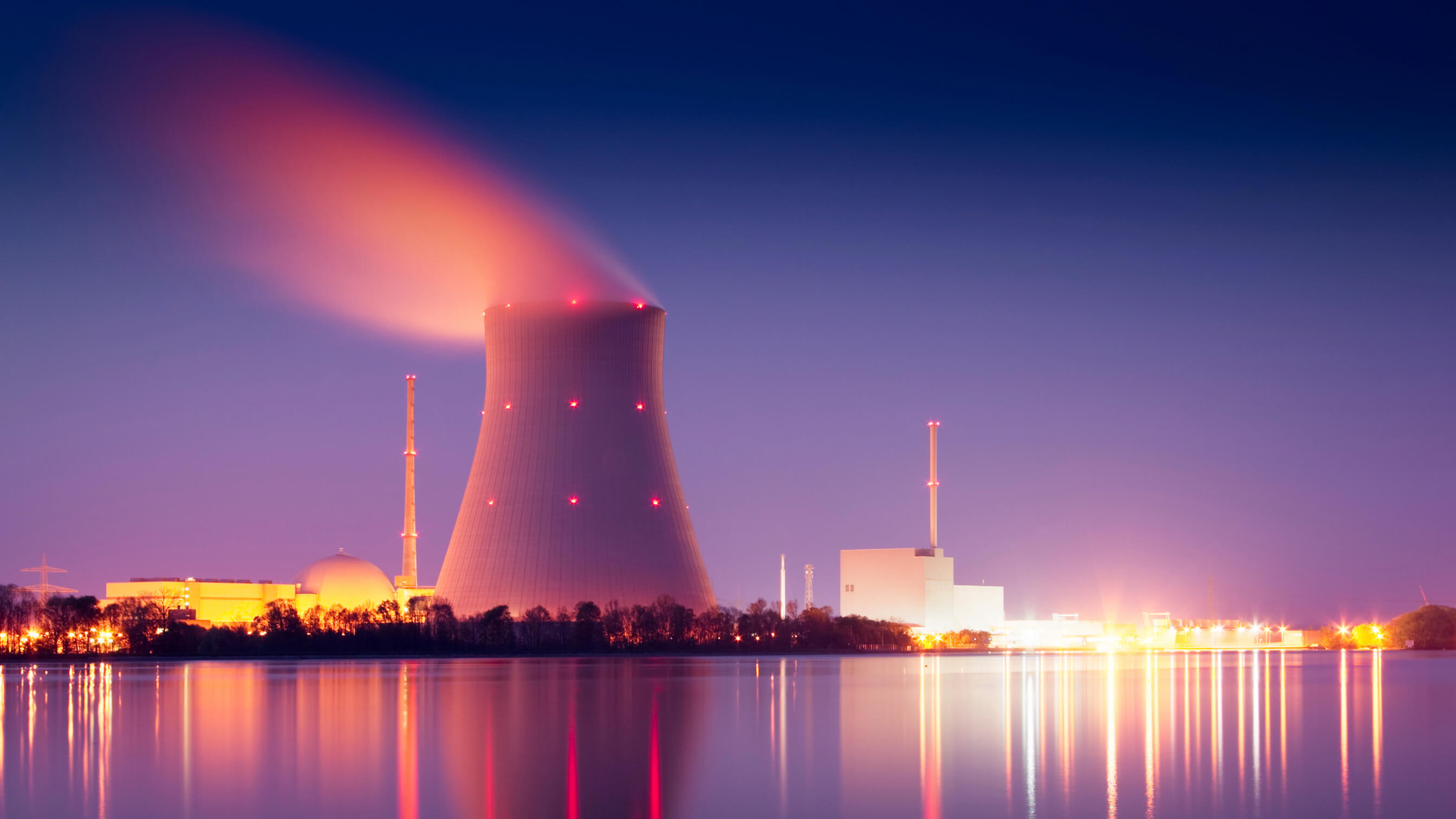 View across water to a nuclear power plant at night