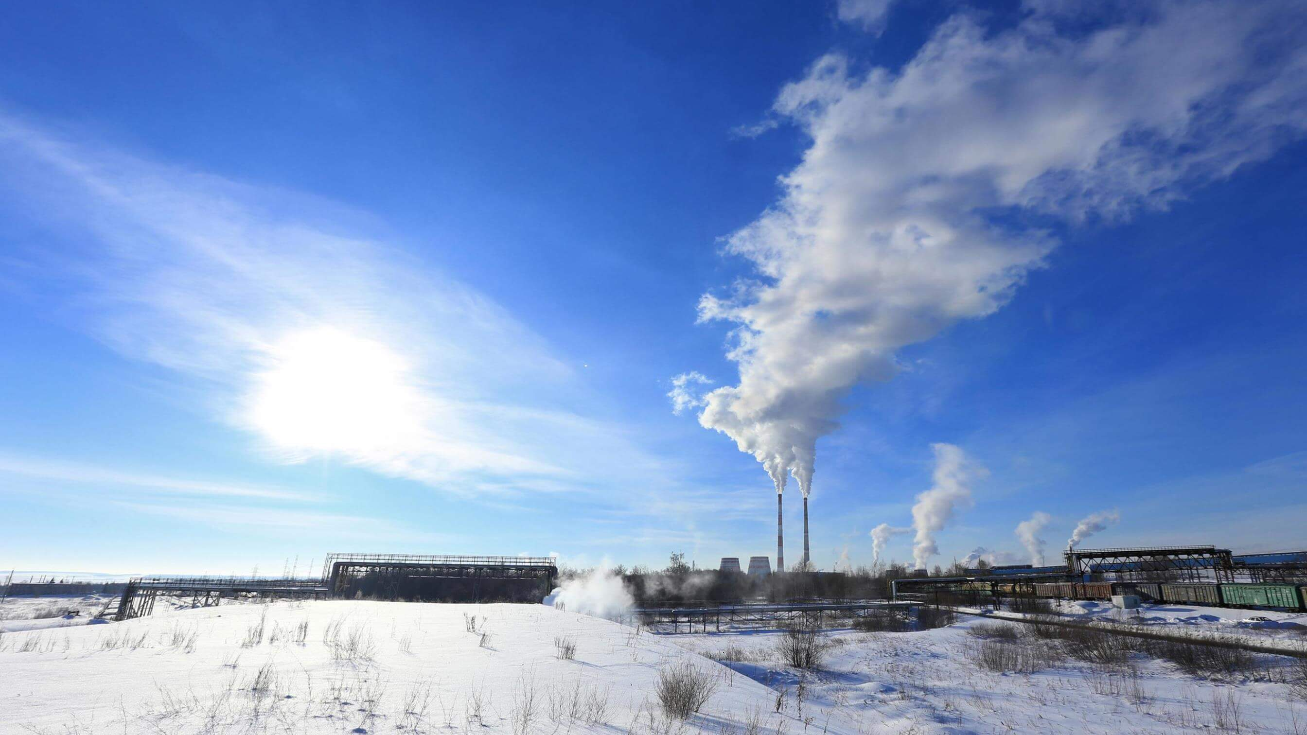 Frozen landscape with oil sands plant and chimneys