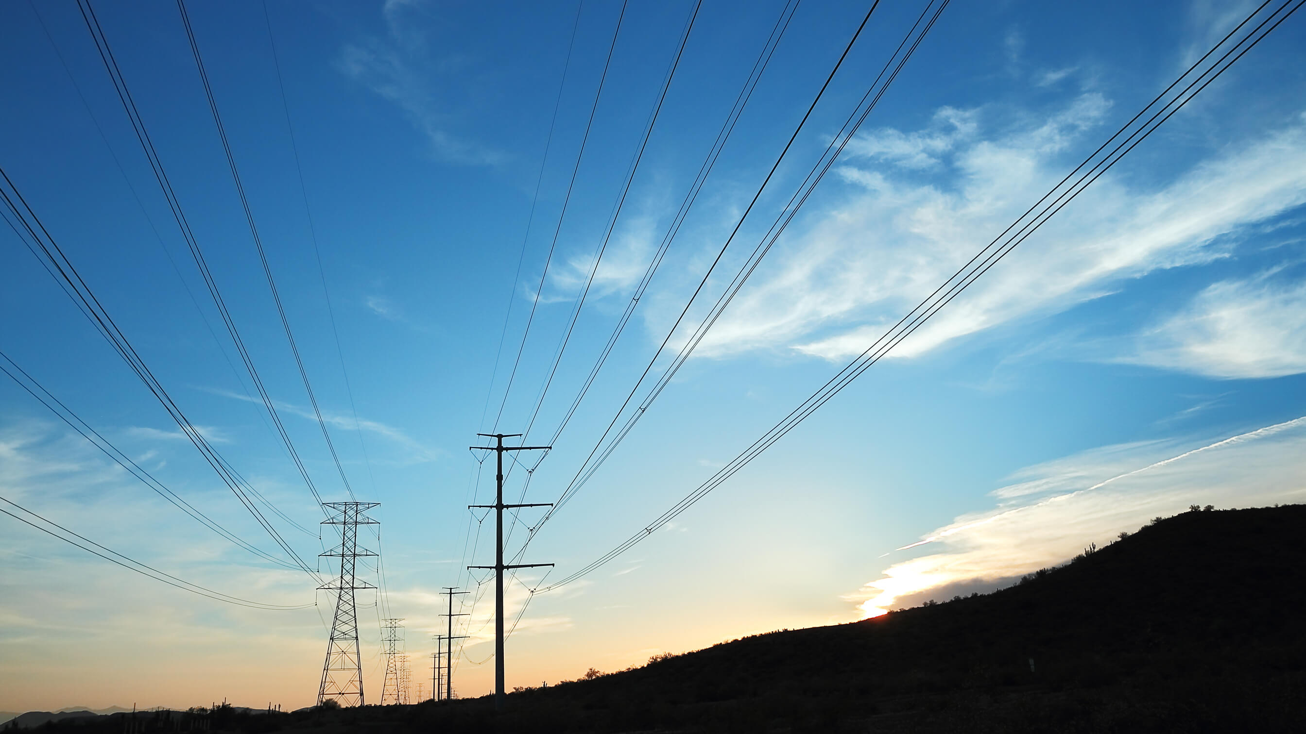 Transmission towers and power lines at sunset