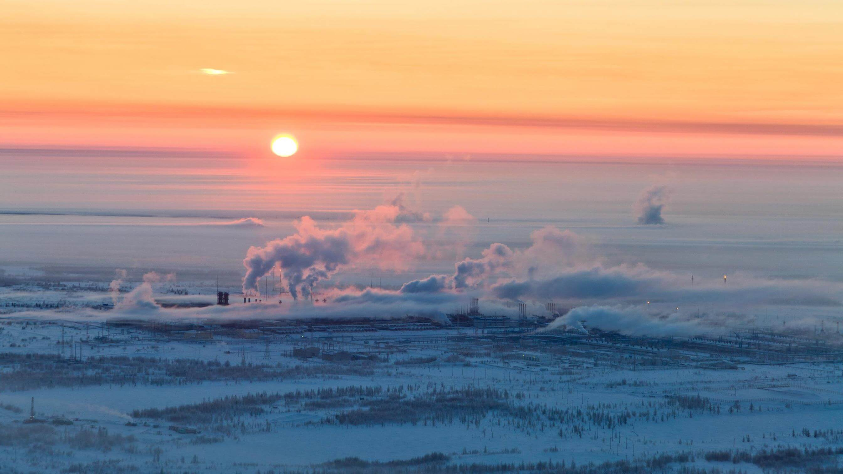 Refinery on frozen tundra at sunset