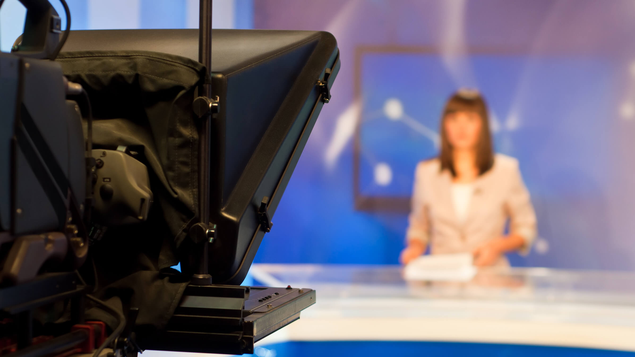 Television camera filming a news presenter