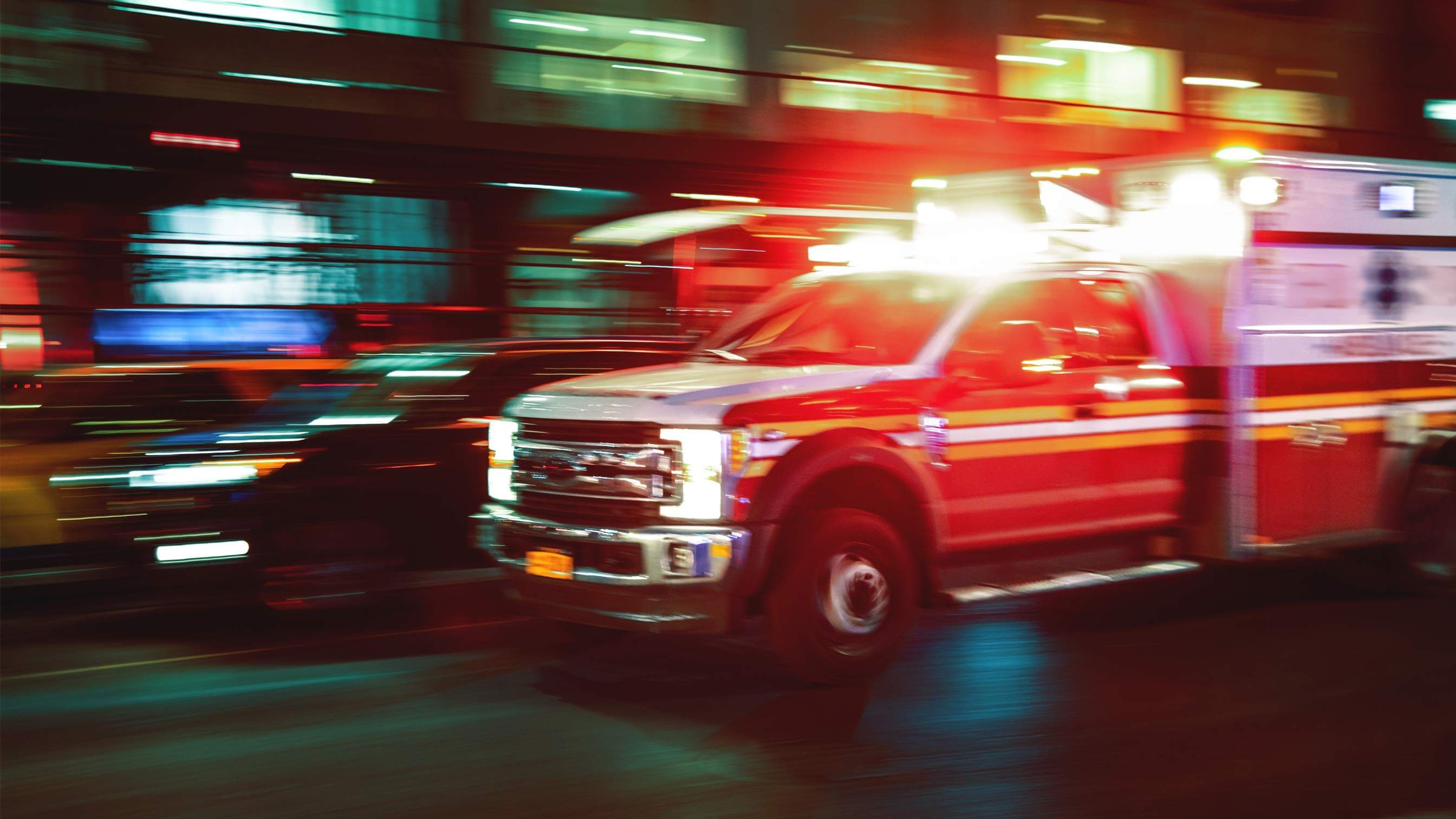 American ambulance streaking across view with lights shining