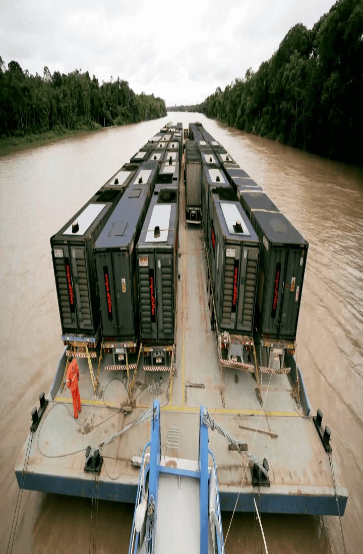 Mobile version of image of boat carrying generators up river.