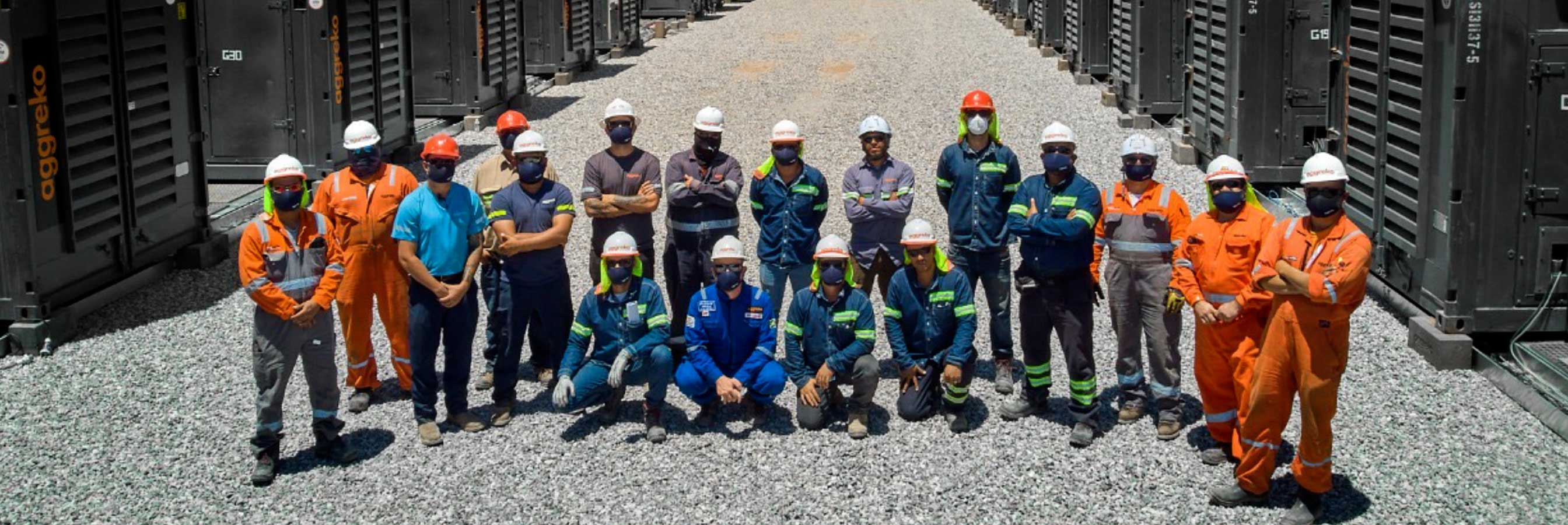 Team of engineers pose in various colour overalls at generator site.