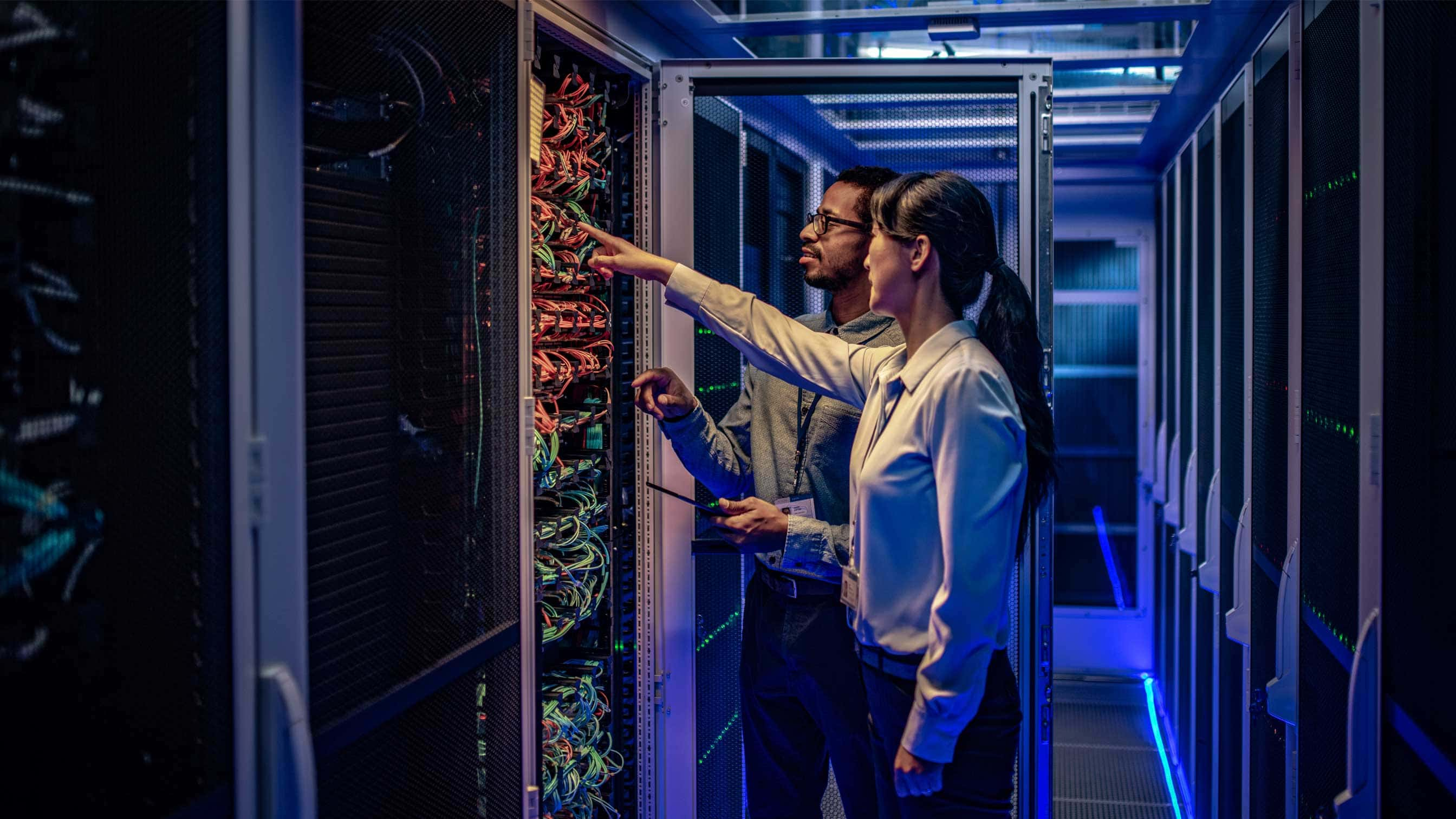 Two experts looking at racks in data centre