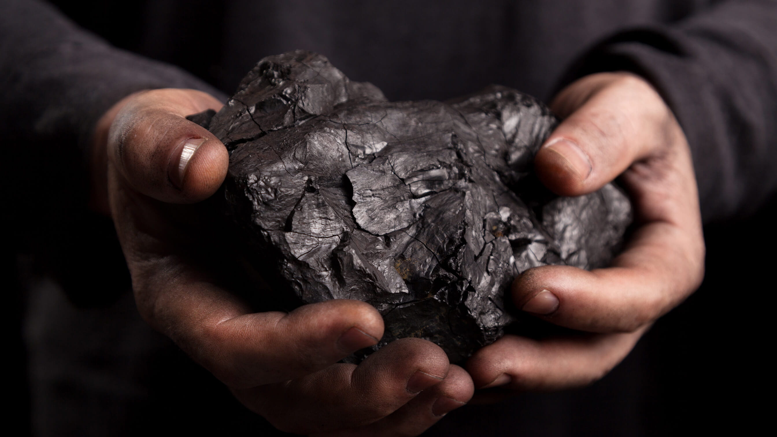 Lump of coal in coal-miner's hands