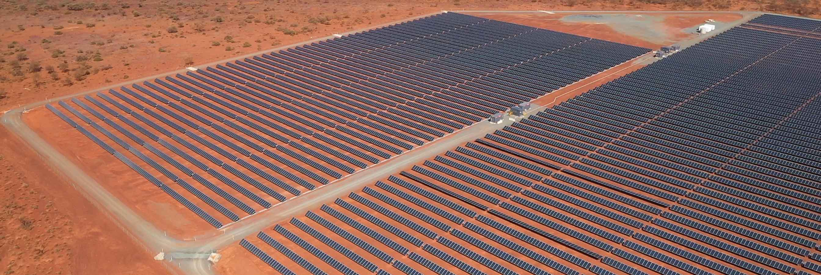 Rows and rows of solar panels located in a remote, hardpan desert-like locale