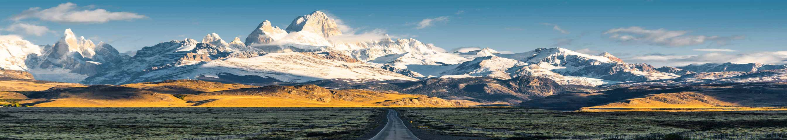 A backdrop of icy mountains, with a road central in view that leads to the craggy vista