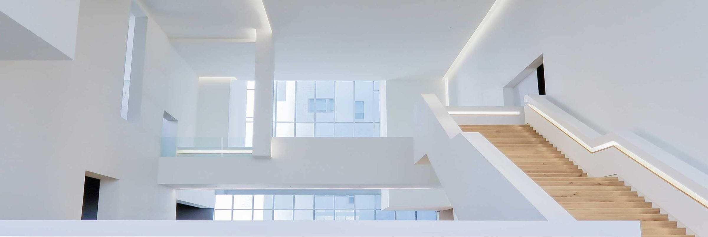 A white interior of a house with a staircase and a long window