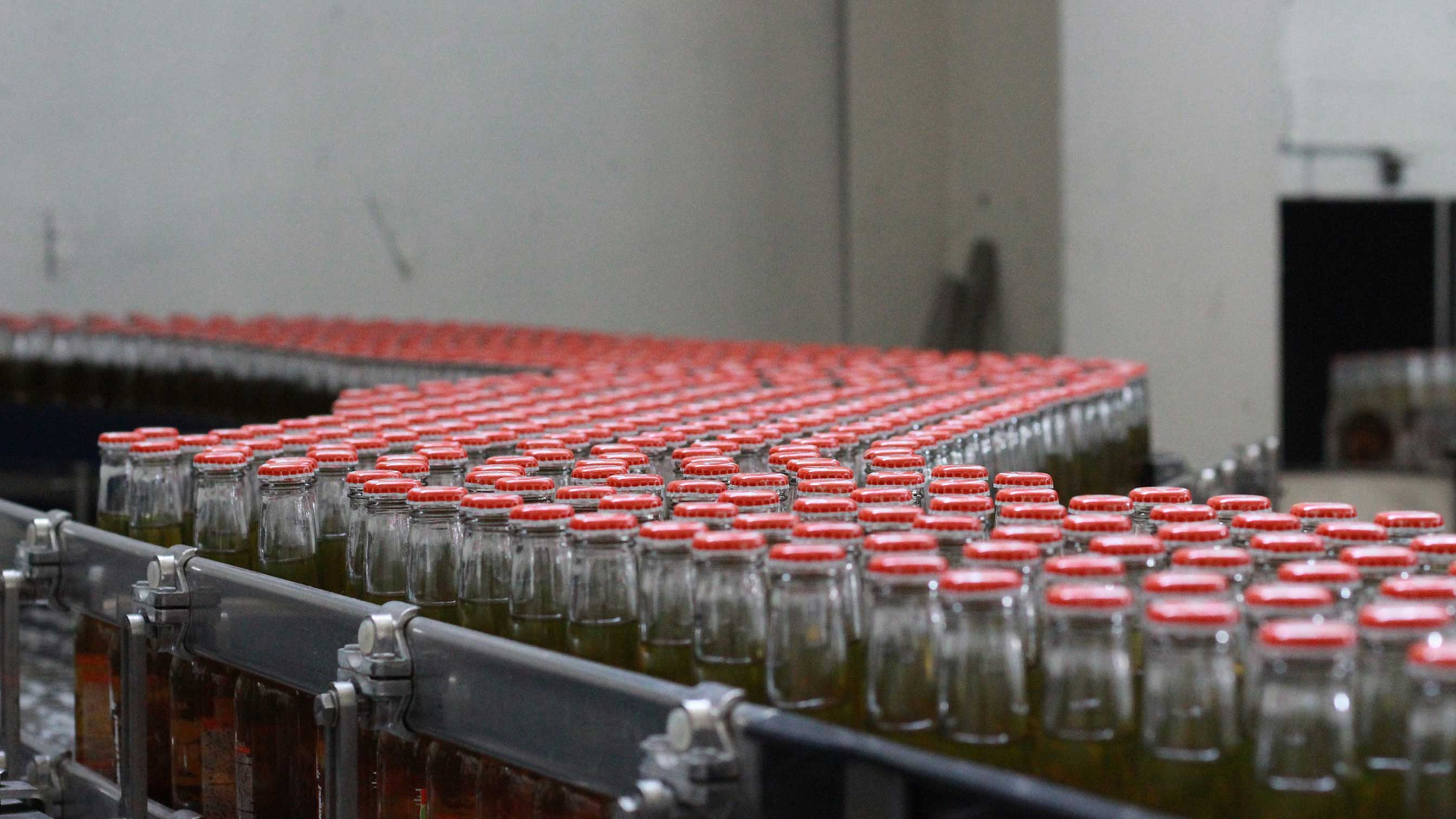 red-topped bottles on production line en masse