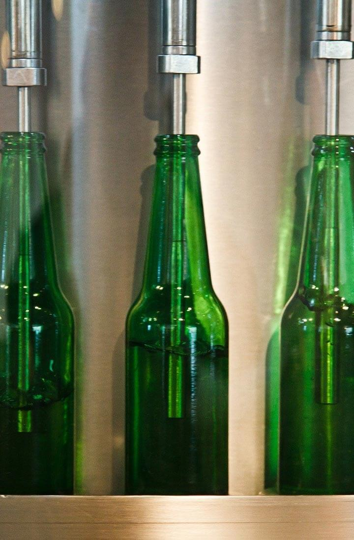 Close up of three green bottles on production line