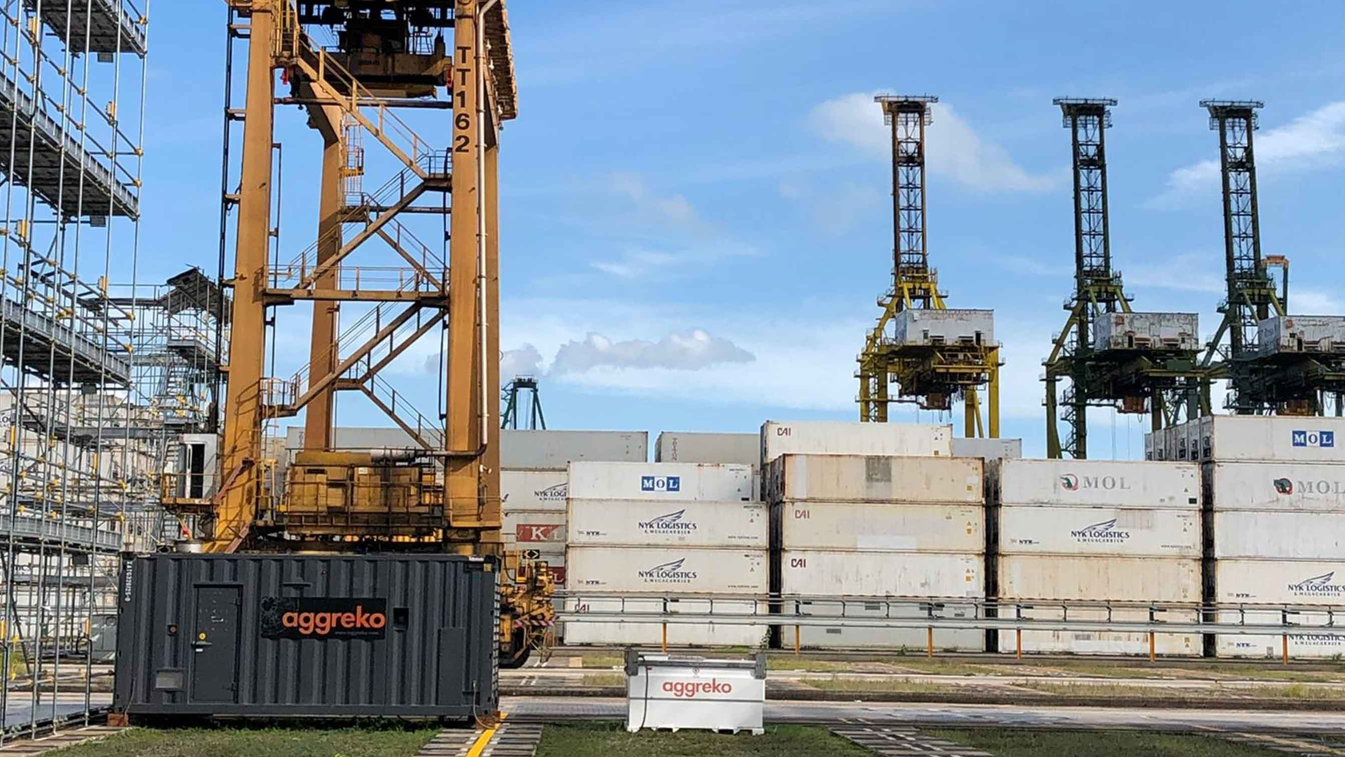 Aggreko generator with containers in the background and a crane at the docks